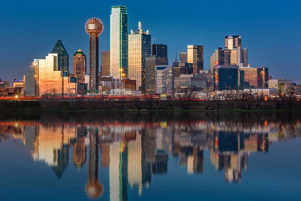 The classic Dallas, Texas skyline at dusk, with reflections in the Trinity River